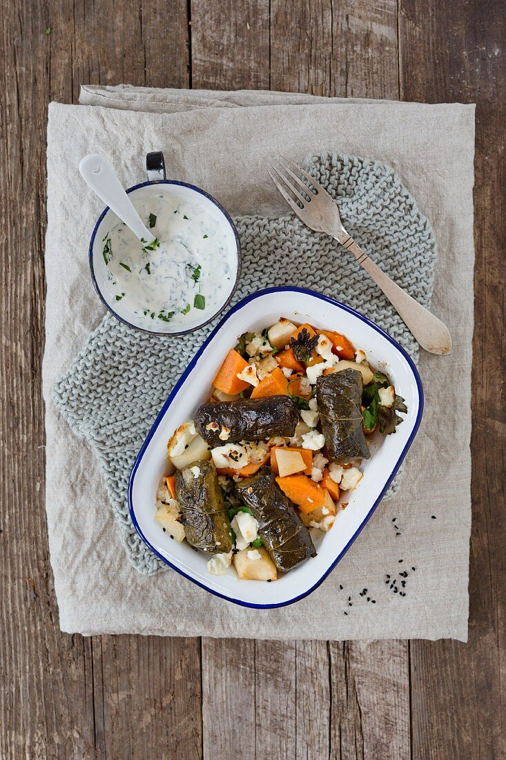 Sweet potatoes with stuffed vine leaves and sheep's cheese in a baking dish, and a herb yoghurt dip