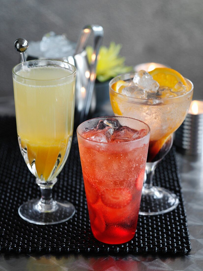 A lemon and orange fizz with cassis, a peach bellini and a shirley temple with strawberries (cocktails)
