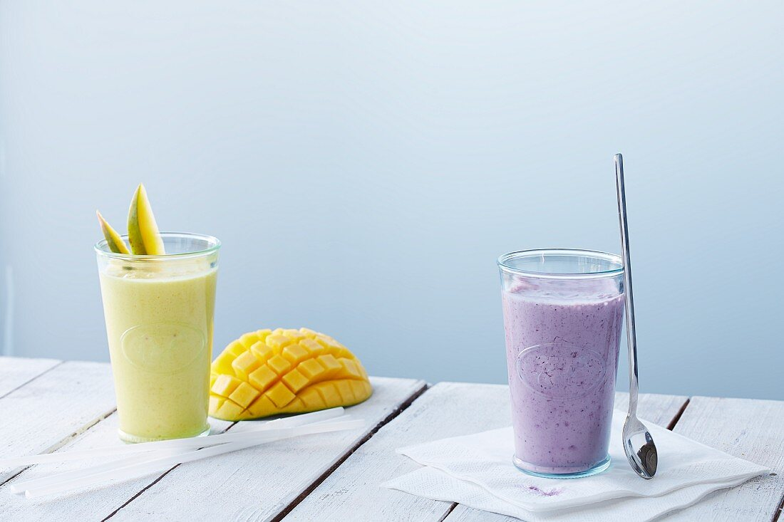 A mango smoothie and a blueberry smoothie in glasses