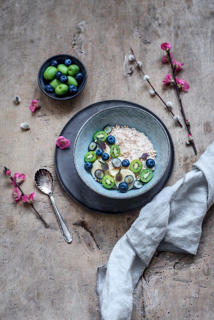 Amaranth porridge with almond milk, quinoa pops, fruit, quince twigs and catkin