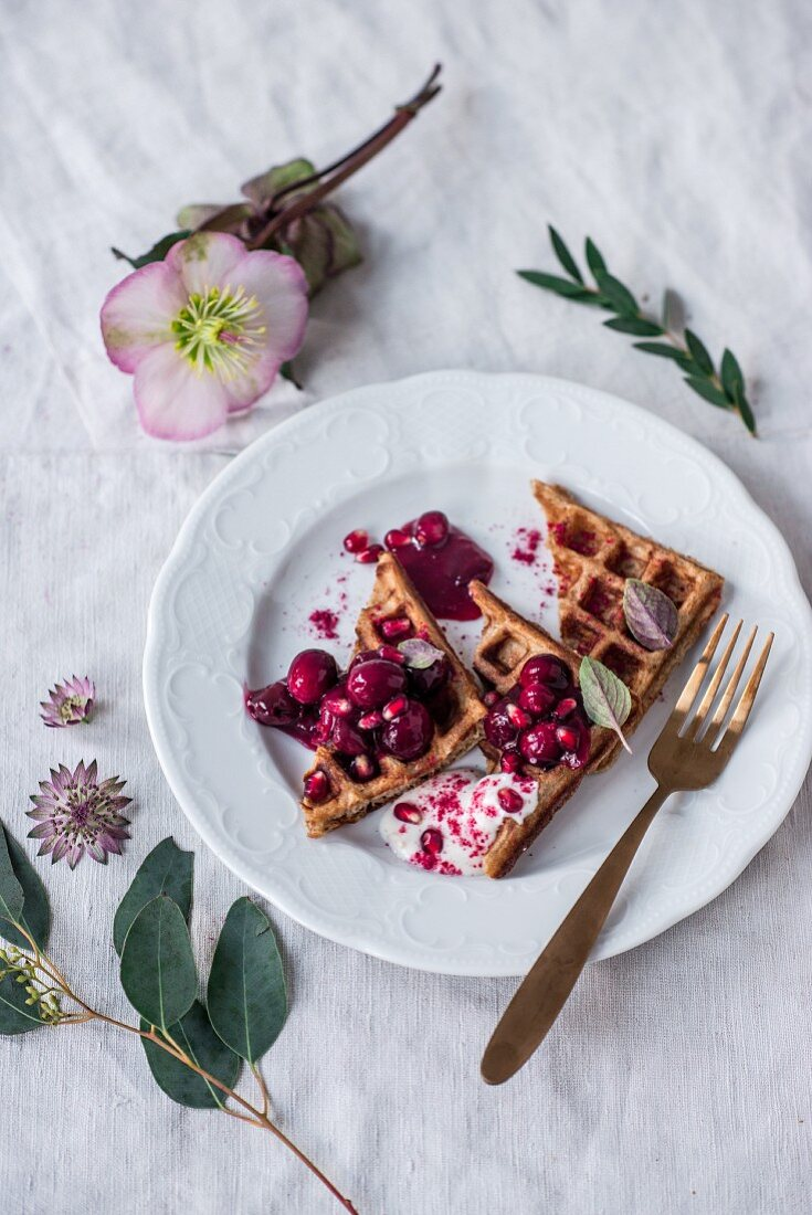 Belgian spelt waffles with warm cherries, cranberries, pomegranate seeds and Christmas roses