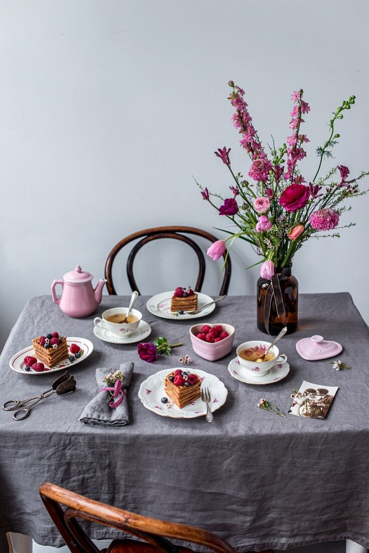 A table set for Valentine's Day with waffles, berries, tea and a flower bouquet