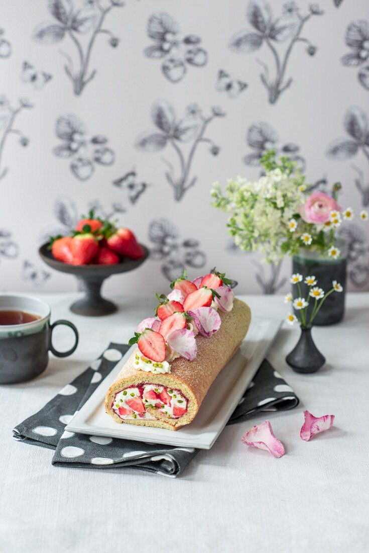 A strawberry and almond sponge roll with rose water, mascarpone cream, pistachios, candied rose petals and flowers