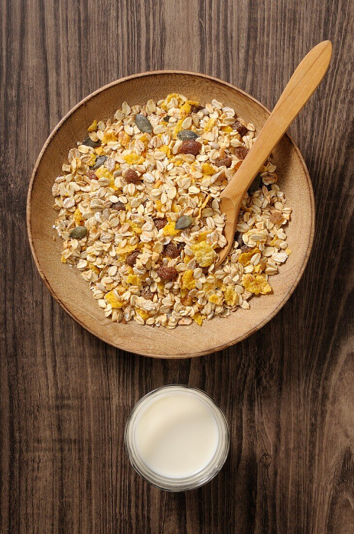 Oatmeal muesli in a wooden bowl with a glass of milk