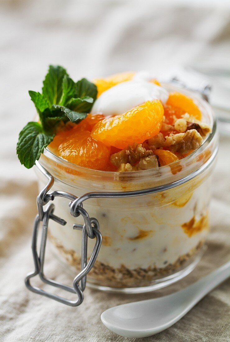 Yoghurt with tangerine segments, oatmeal, nuts, fruit sauce and mint in a mason jar