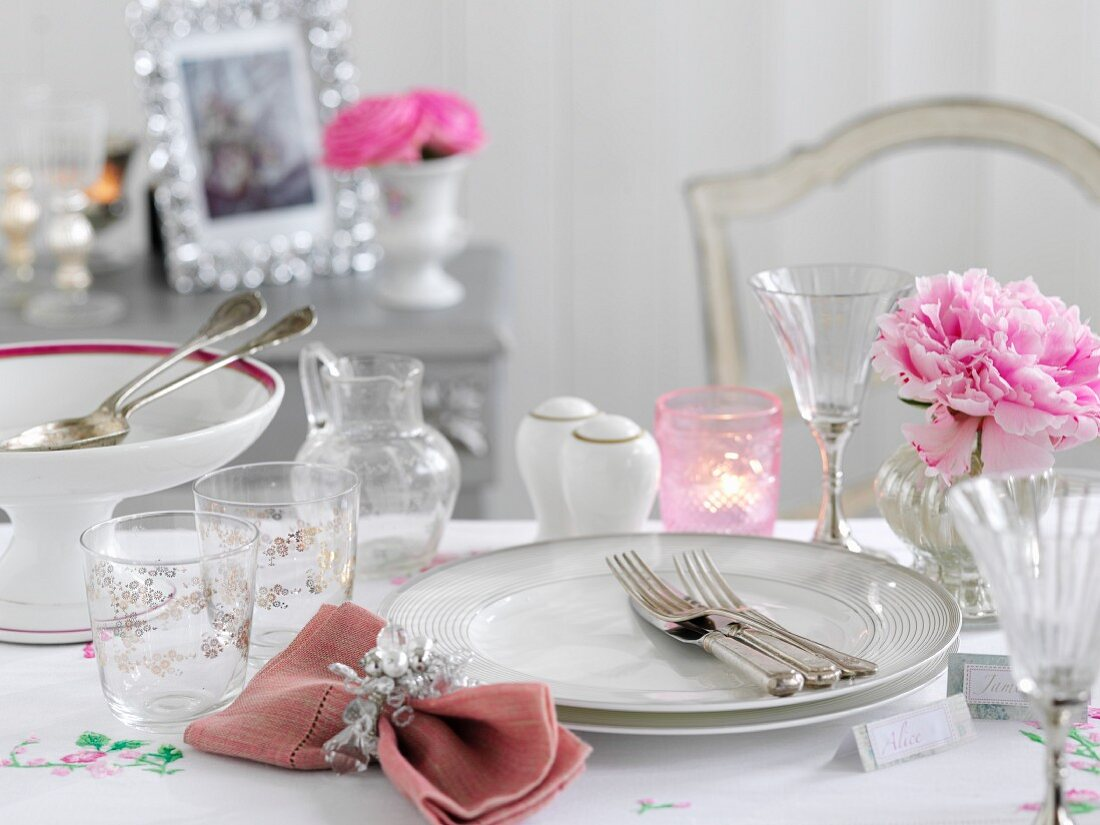 A festive place setting with pink peonies