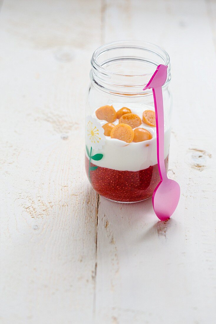 A strawberry chia seed dessert with yoghurt and physalis in a glass jar