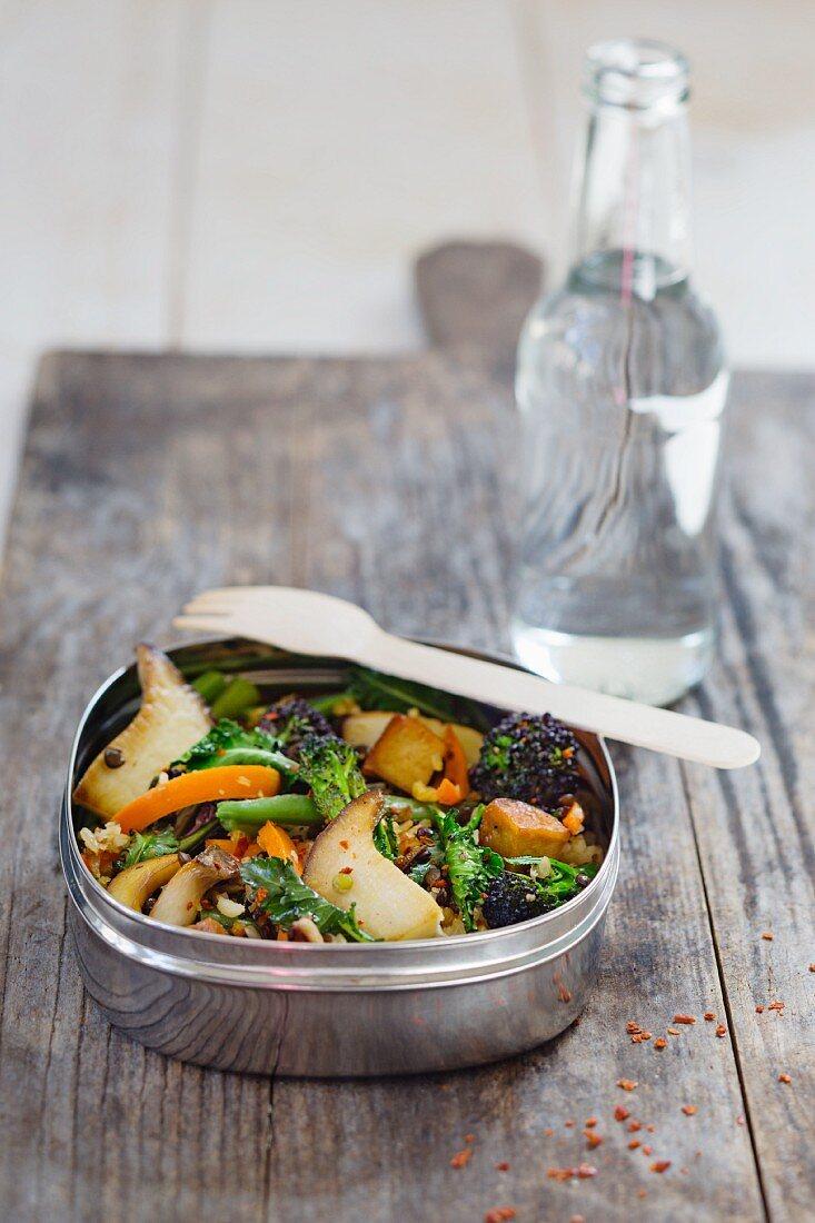 Linsen-Reis-Pfanne mit Pilzen, Karotten und Brokkoli in Lunchbox vor Wasserflasche