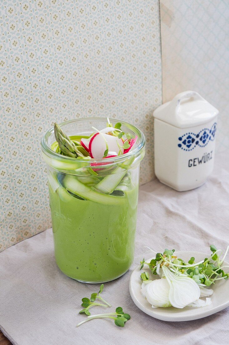 Pea and asparagus cream soup with radish slices in a glass jar