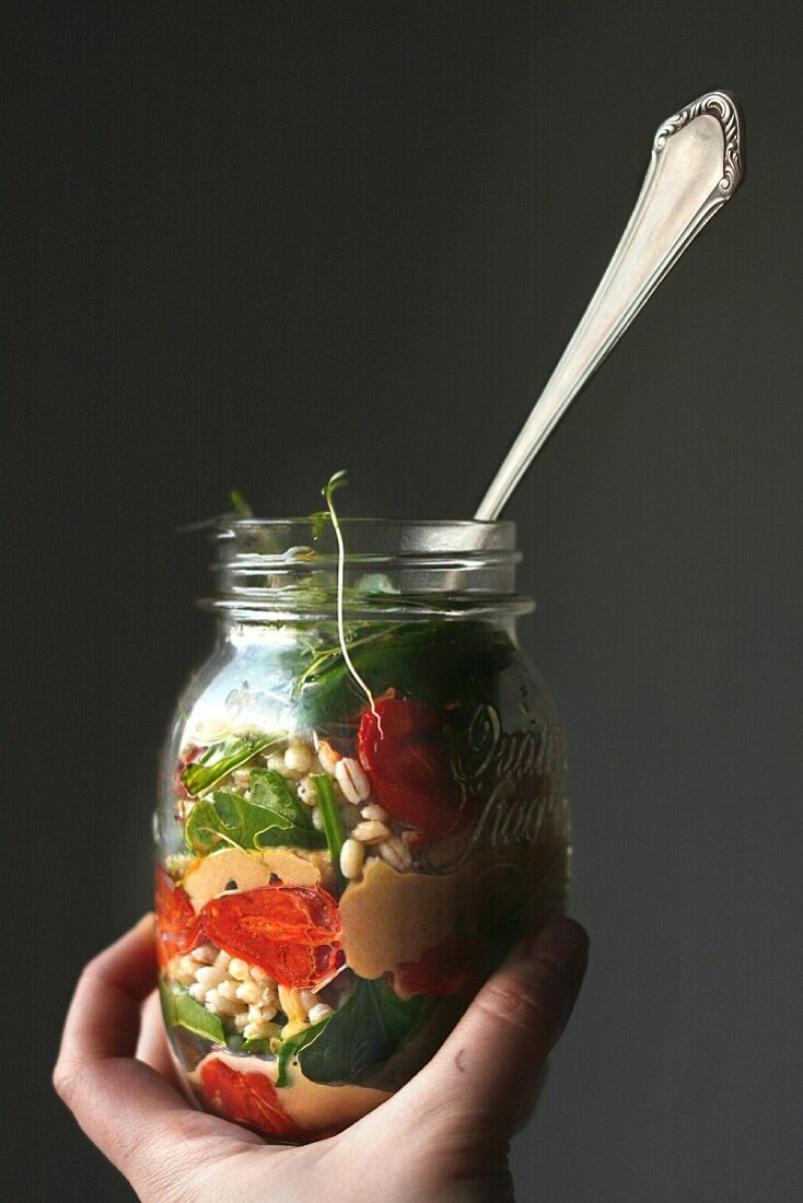 A hand holding a jar of barley salad with balsamic vinegar, roasted tomatoes, baba ghanoush, spinach, cress and almonds