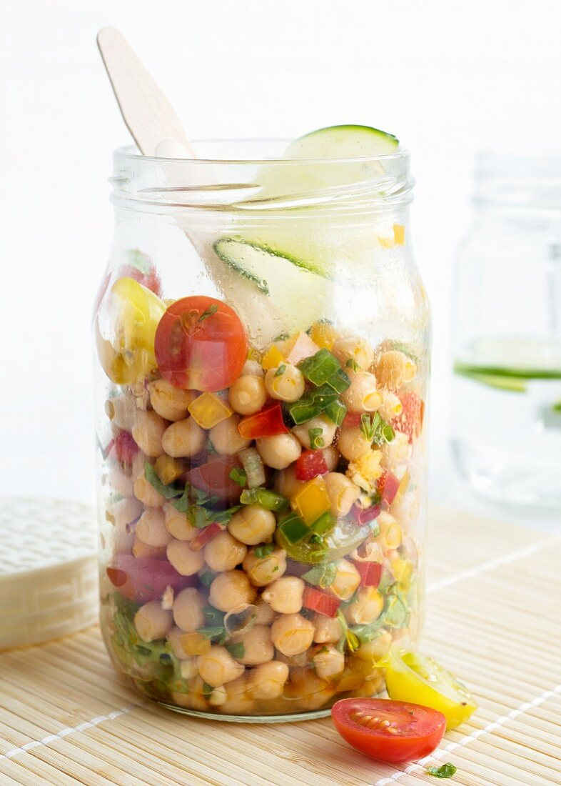 A chickpea salad in a glass jar with tomatoes, peppers, red onions, spring onions, spices, limes, olive oil and fresh parsley