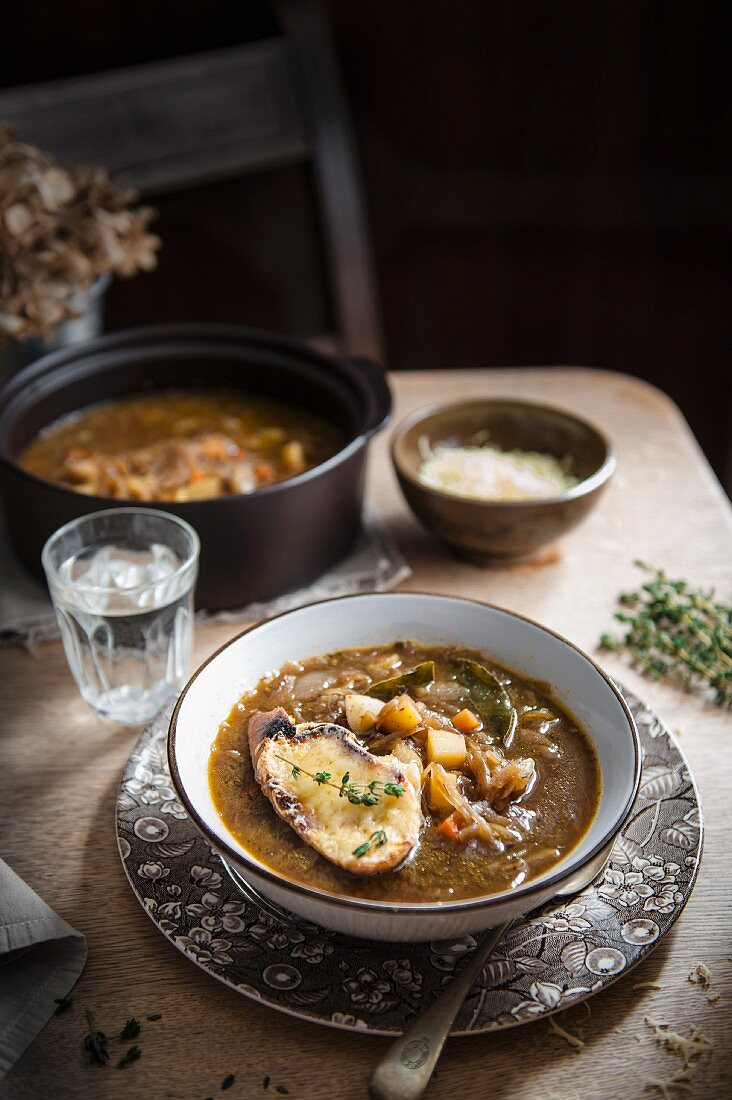 Onion soup with a cheese baguette crouton and herbs