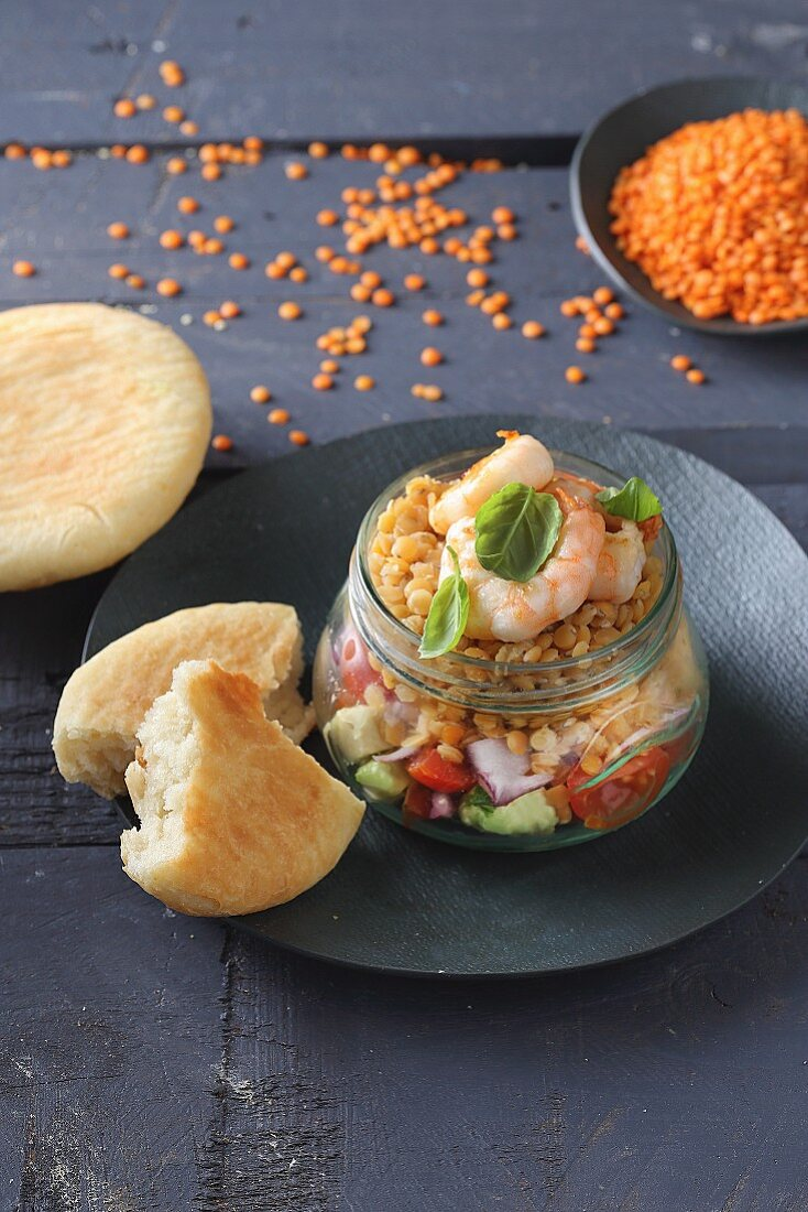 Avocado salsa with lentils and shrimps in a glass jar
