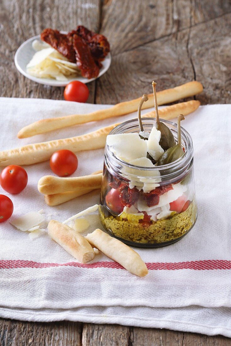 Giant caper salad with tomatoes and Parmesan in a glass jar, with grissini