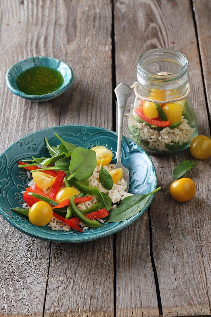 Brown rice salad with yellow cherry tomatoes, peppers and spinach
