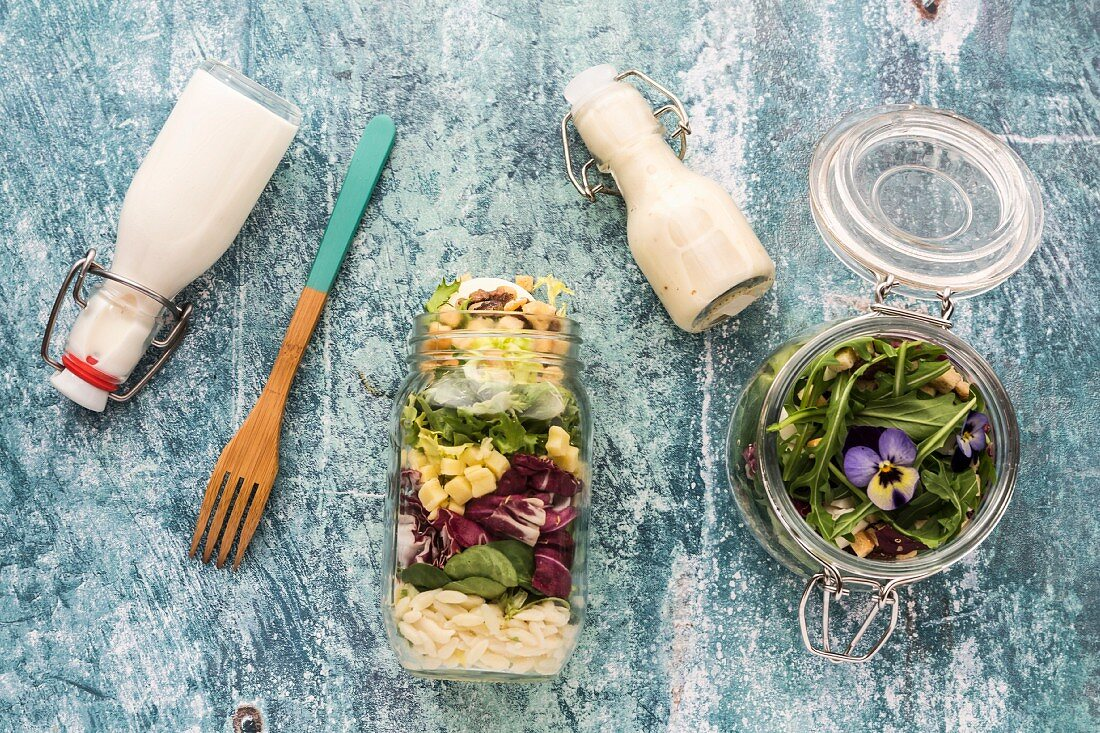 Quinoa and orzo pasta salads in glass jars, with dressing and a wooden fork