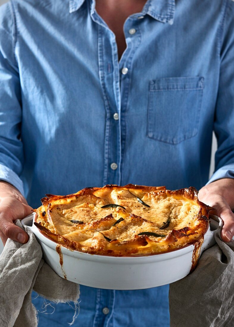 A man holding a dish of lasagne fresh from the oven