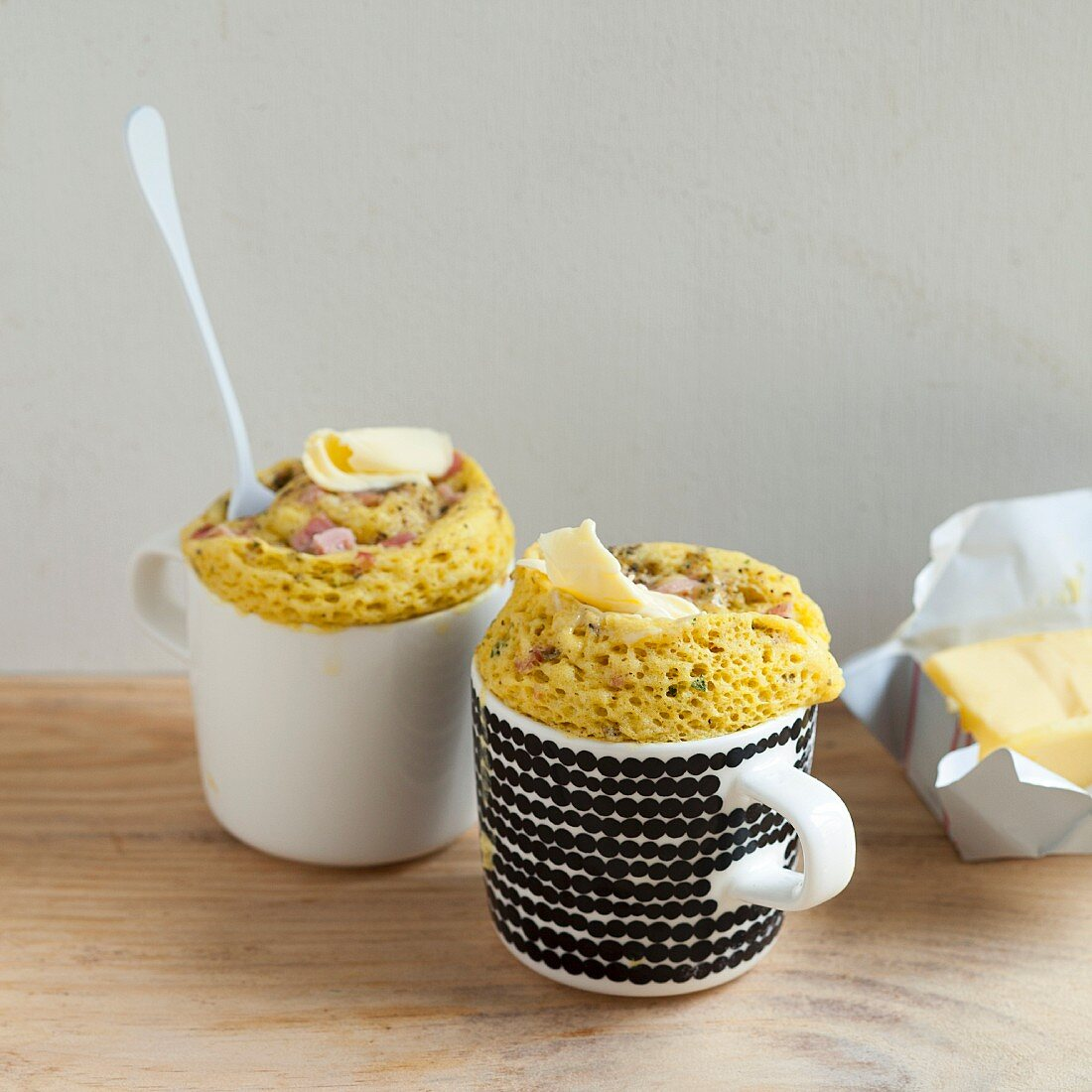 Savoury mug cakes with diced ham and a dab of butter on the top