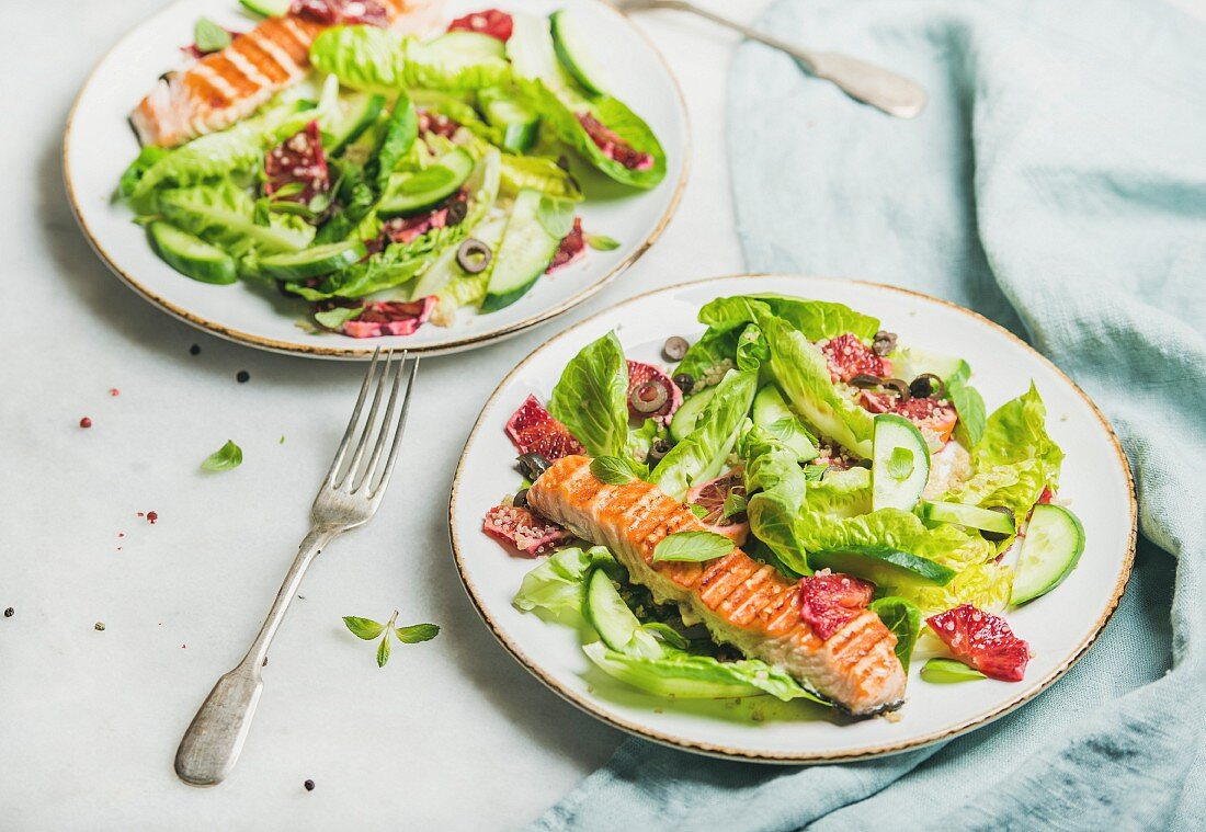 Healthy energy boosting spring salad with grilled salmon, blood orange, olives, cucumber and quinoa