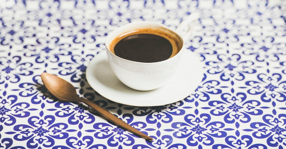 Cup of black Eastern style coffee over oriental bright Moroccan patterned background