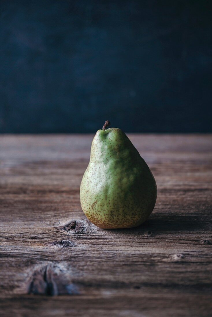 Single pear on a rustic wooden table