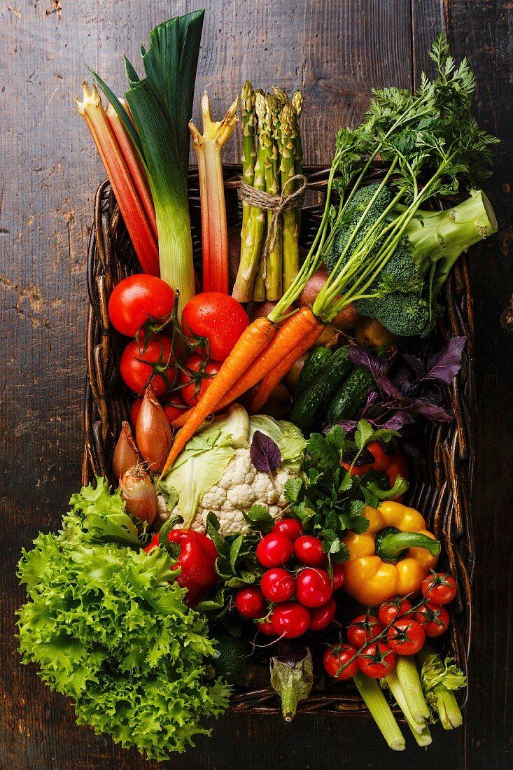 Fresh vegetables in basket on wooden background