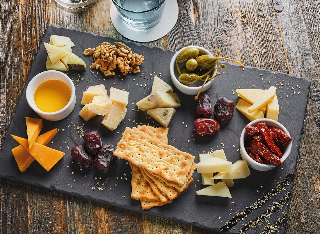 Käseplatte serviert mit Crackern, Nüssen, Kapern und getrockneten Tomaten