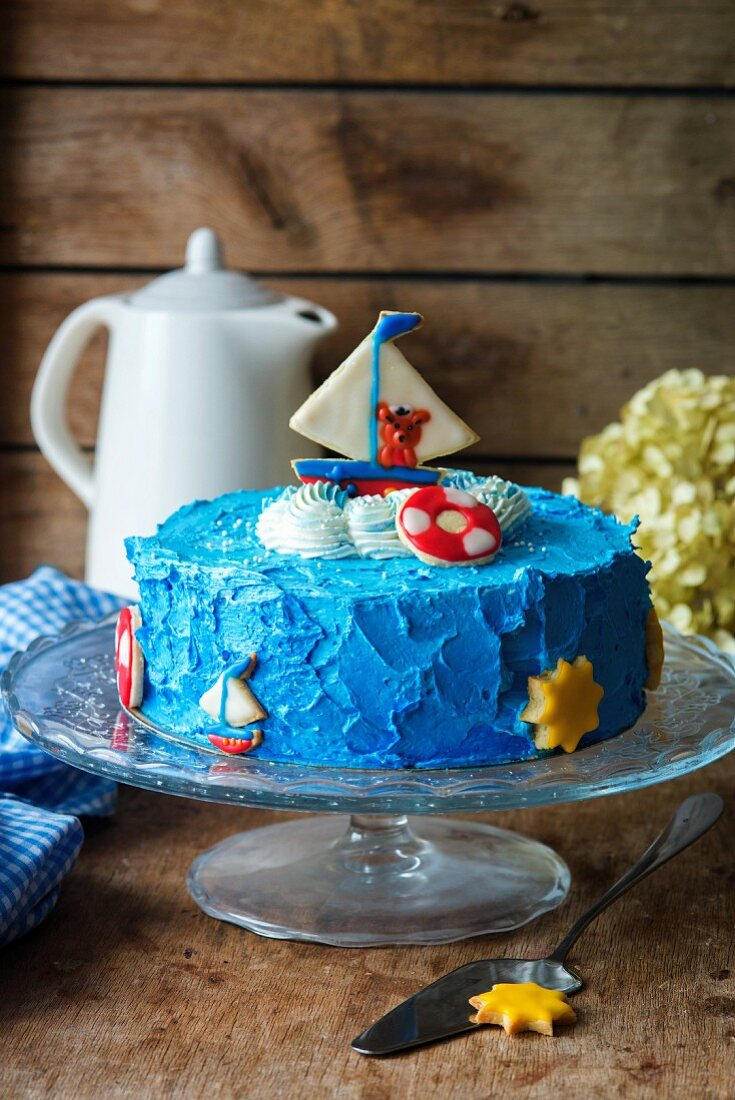 A children's cake decorated with a sailing boat and a bear