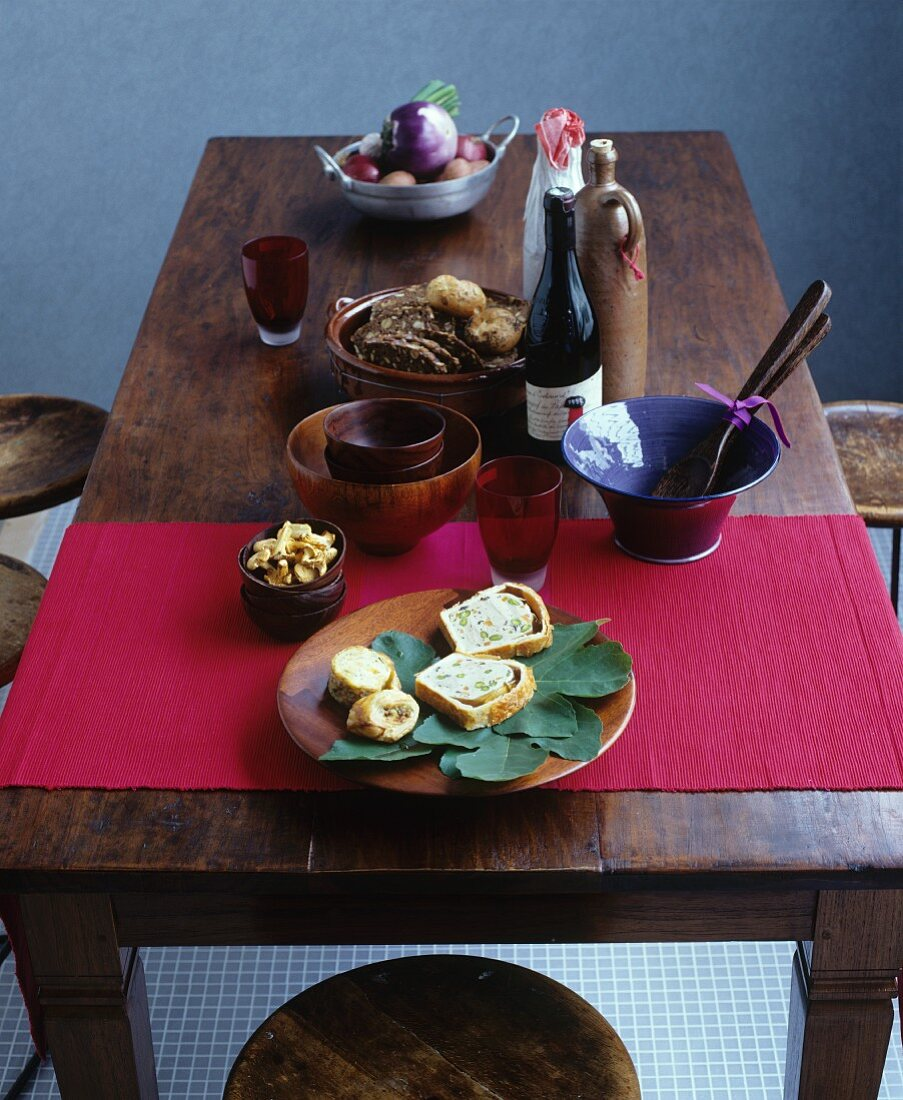 Autumnal terrine, wine and bread on a rustic wooden table