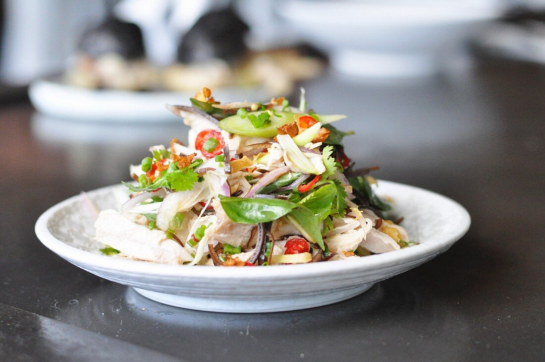Chicken salad with vegetables and herbs on a plate