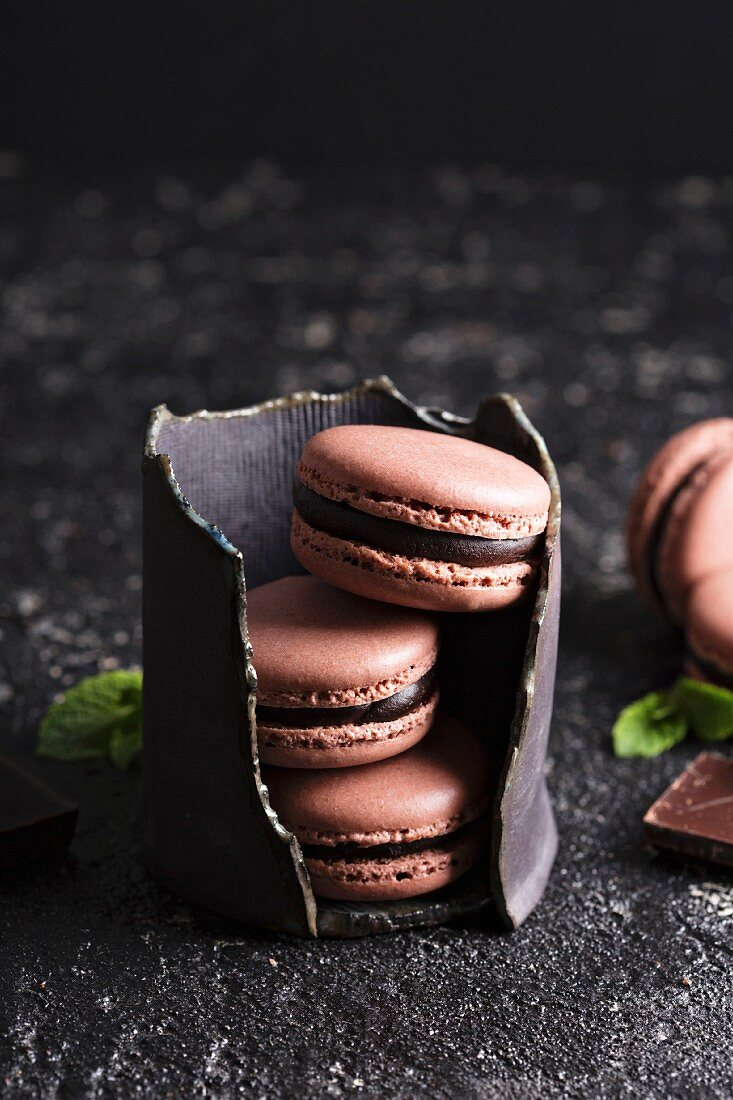 Chocolate french macarons with ganache filling on a black table