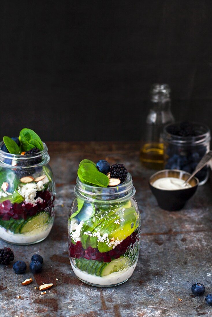 Vegetable salads with berries and yoghurt dressing in glass jars