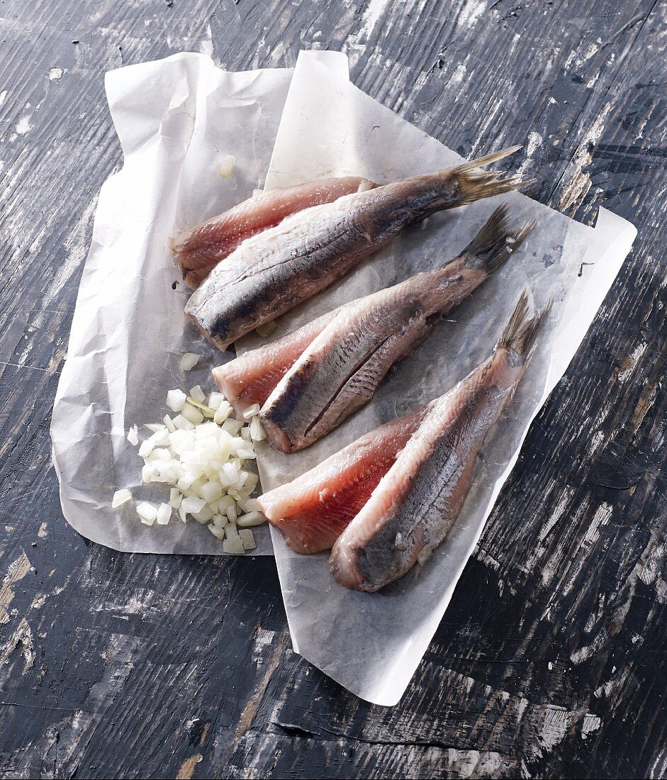 Three herrings on paper with diced onions