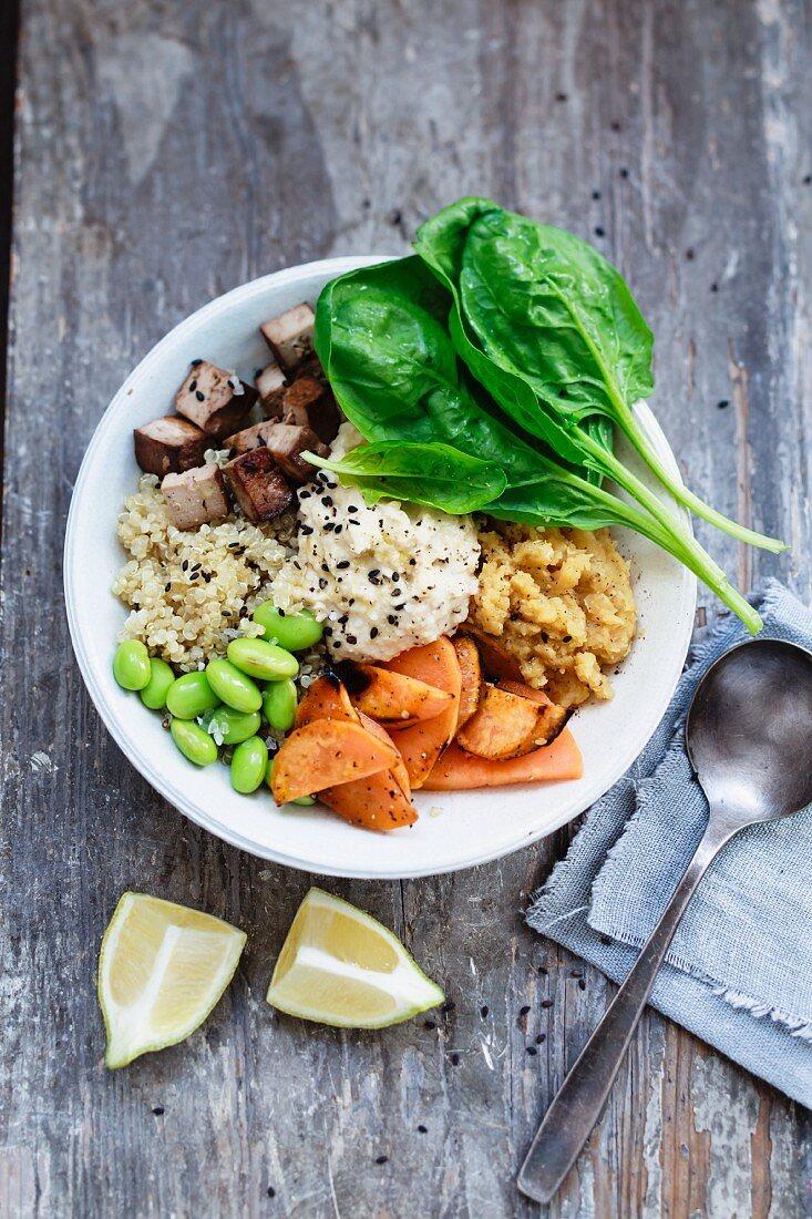 A buddha bowl with quinoa, lentils, sweet potato, edamame, tofu, spinach and hummus