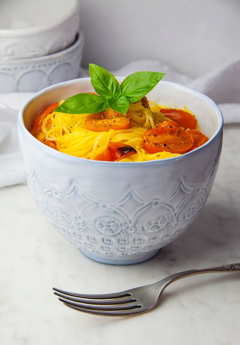 Gluten-free capellini pasta with roasted tomatoes and basil in a bowl