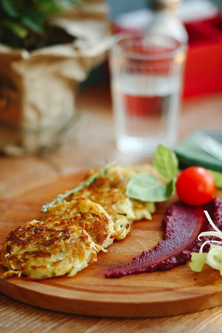 Potato and vegetable fritters on a wooden chopping board