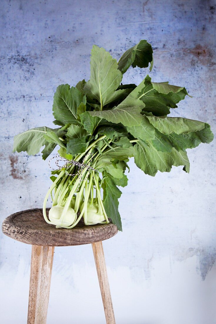 Fresh kohlrabi with leaves on a wooden stool