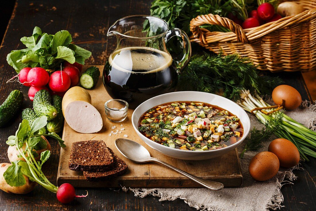 Cold Soup Okroshka with sausage, vegetables and kvass serving size in bowl and raw ingredients on wooden table