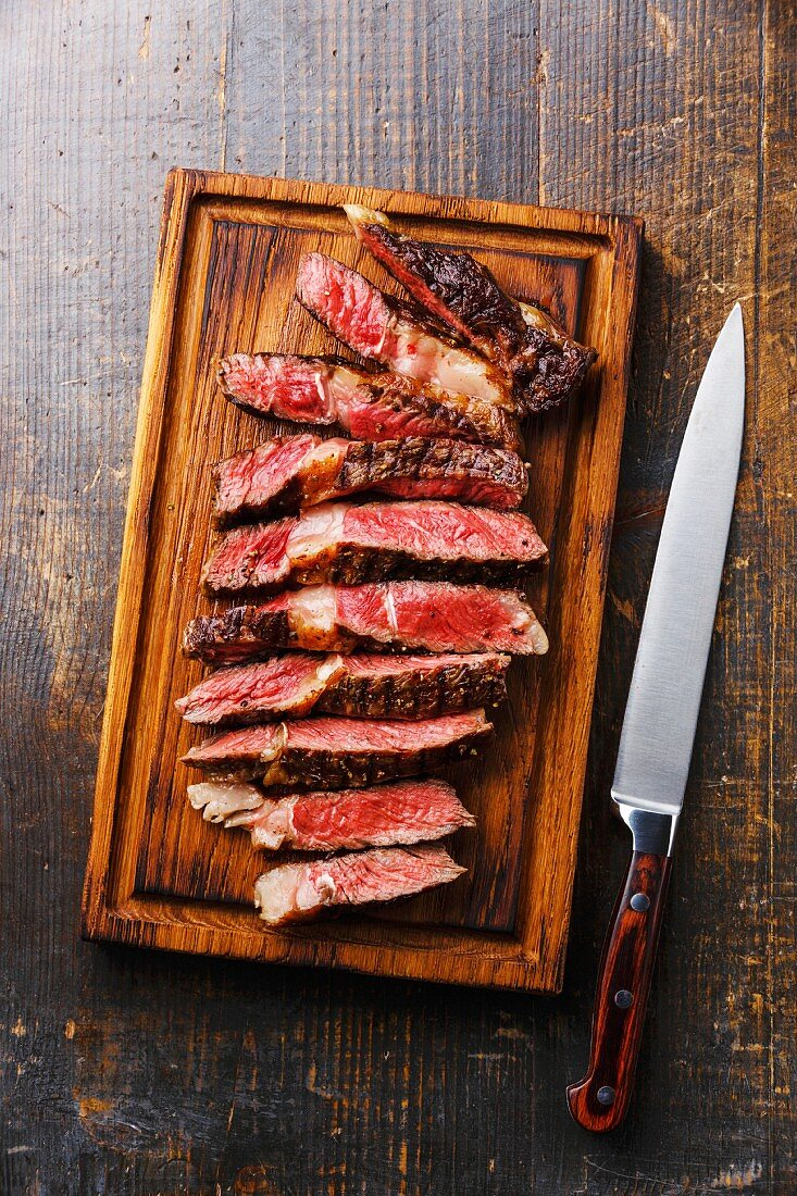 Sliced medium rare grilled beef Ribeye steak on cutting board and kitchen knife on wooden background
