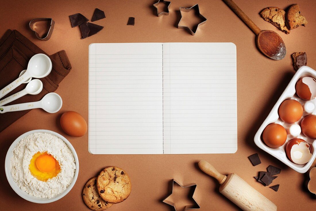 Baking background with ingredients for making chocolate chip cookies and recipe book