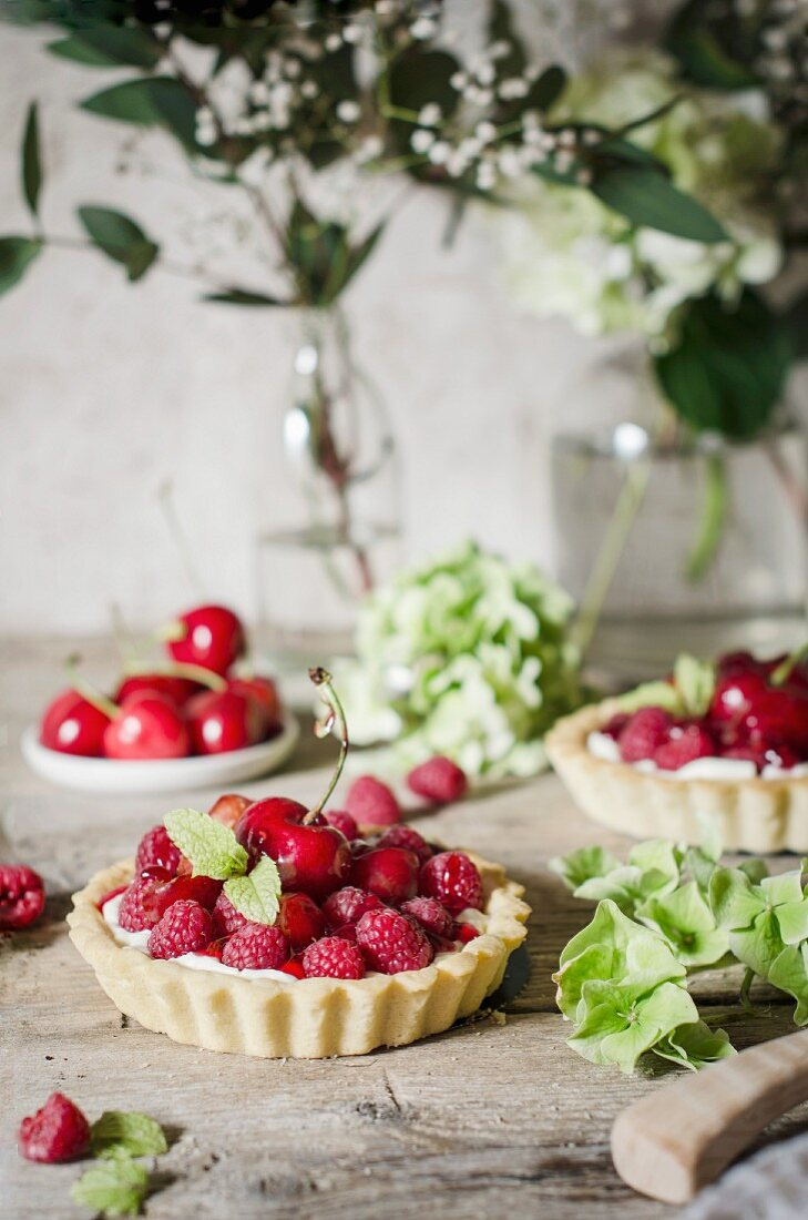 A cherry and raspberry tart on a kitchen table.