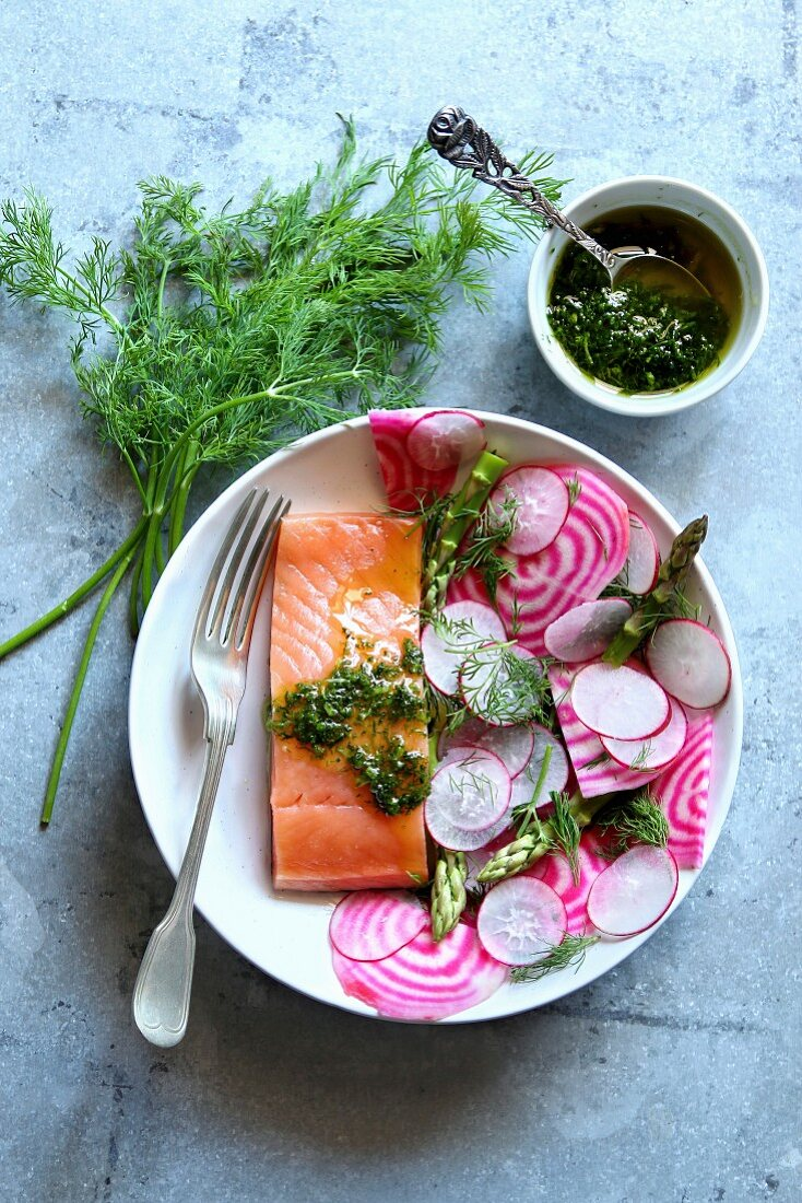 Spring salad with radish, chioggia beet, asparagus with a piece of smoked salmon and dill dressing on a plate