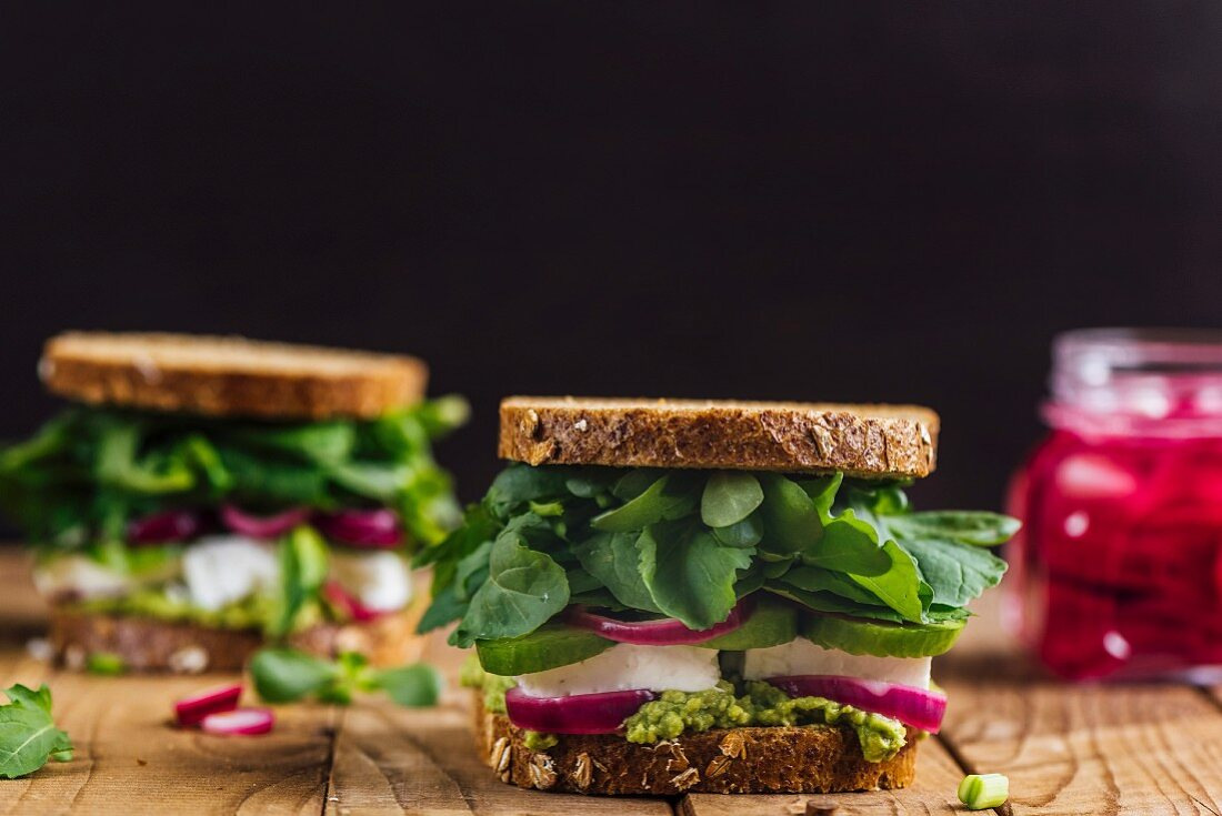 Springtime feta sandwiches with avocado, pickled red onions and herbs like arugula, purslane and fresh mint