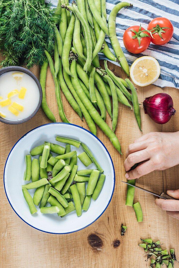 A woman chopping fresh fava beans to make Mediterranean style fava beans