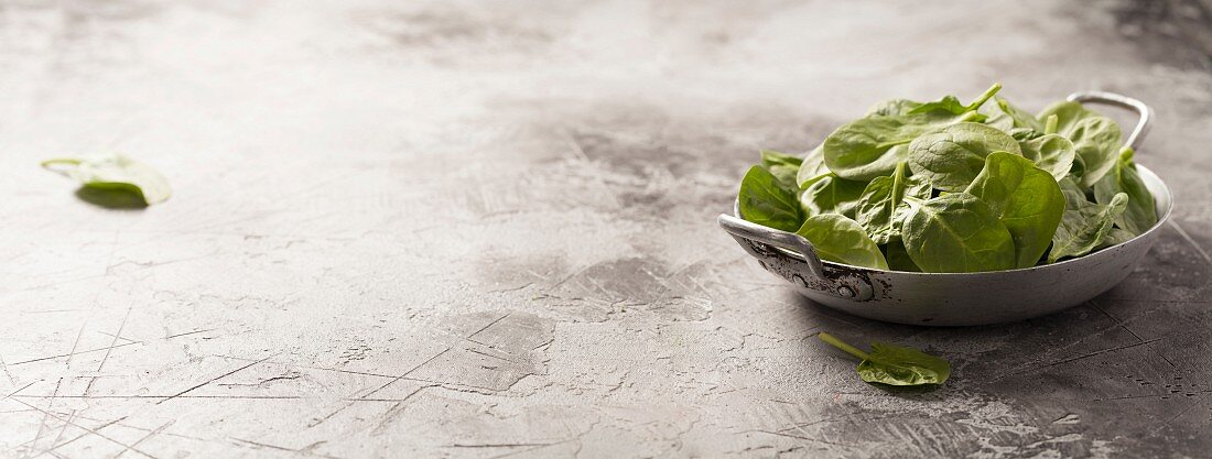 Frischer grüner Spinat auf rustikalem Hintergrund