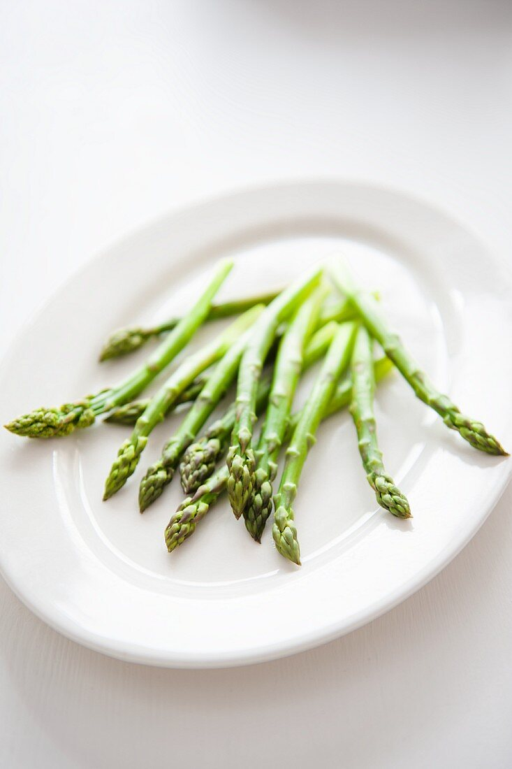 Uncooked green asparagus on a white serving platter