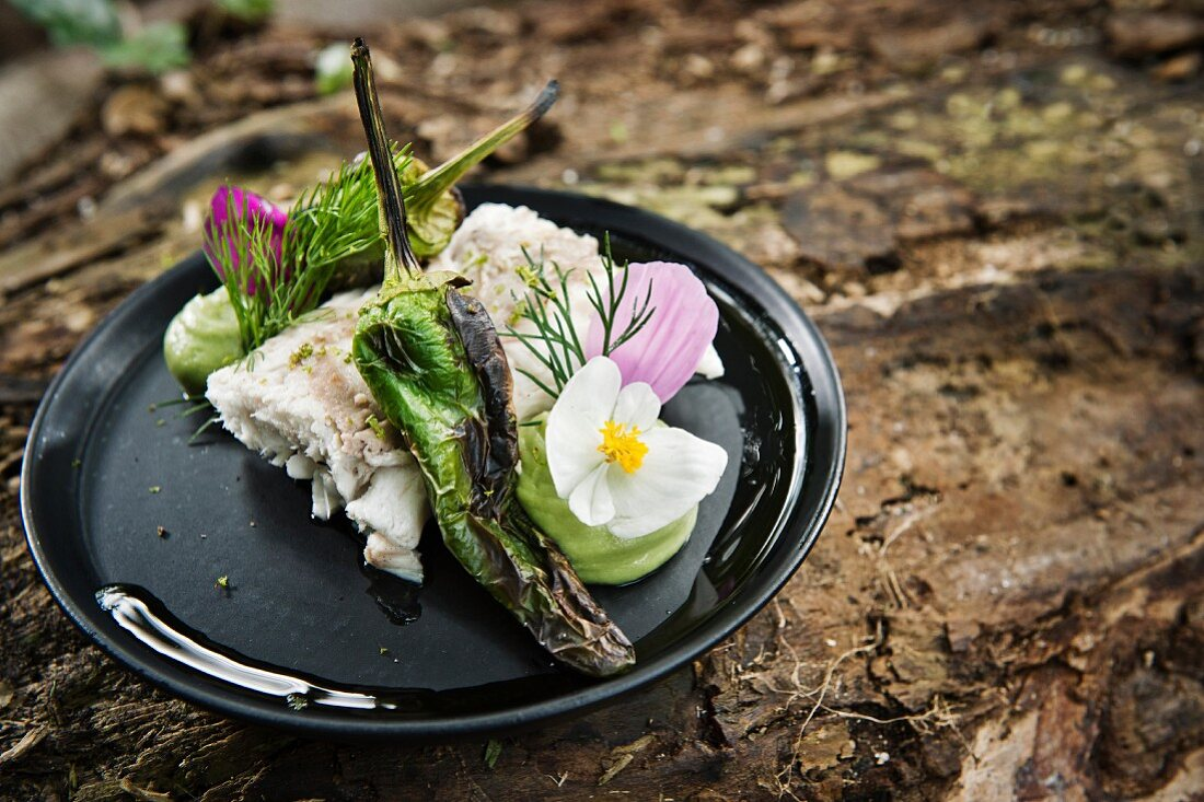A fish fillet with grilled chillies served with flowers on a camping plate