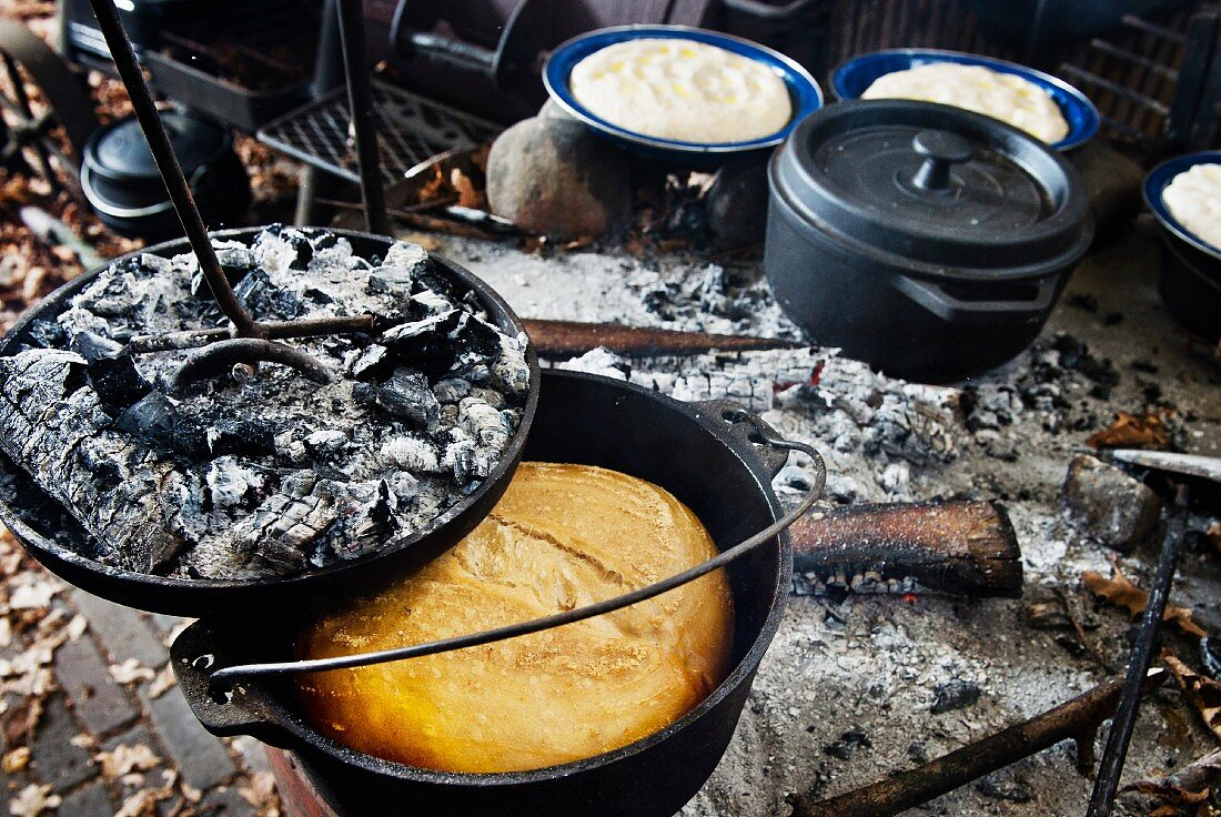 Baking bread in a Dutch oven over a fire place (camping)