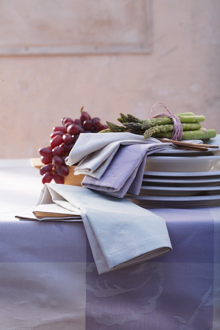 Green asparagus, grapes and fabric napkins on a pile of plates