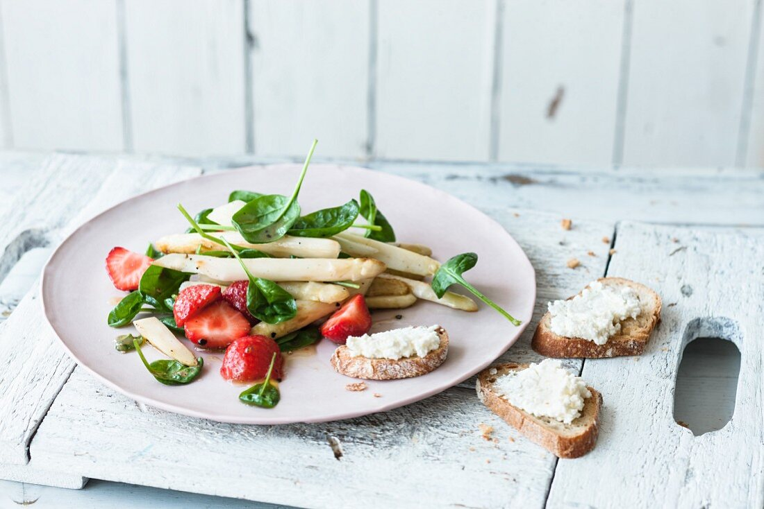 Asparagus and strawberry salad with baby leaf spinach and feta crostini